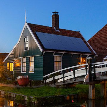 house next to canal with solar panels