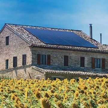 European house with solar panels surrounded by sunflowers