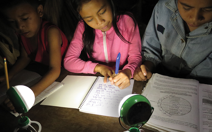 Young girl doing homework by a Nokero solar powered lamp