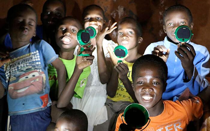 Childrens Holding Nokero Solar Powered Lamps