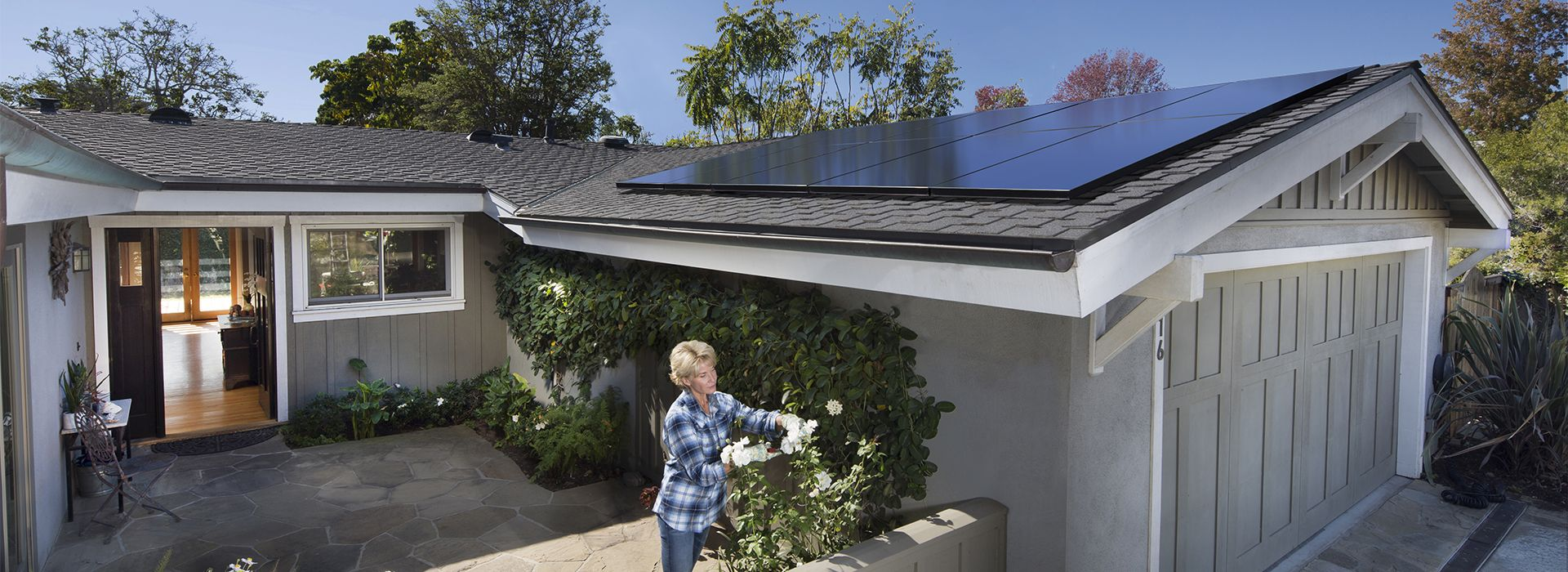 woman pruning roses in front of home with sunpower solar panels