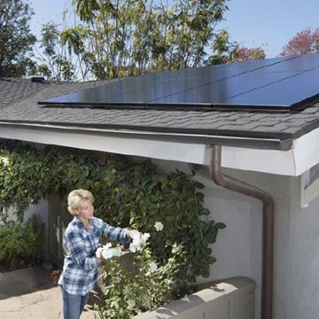 lady in garden of her solar powered house