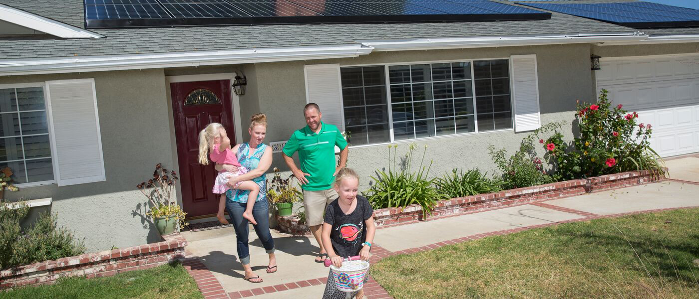family leaving solar-powered house