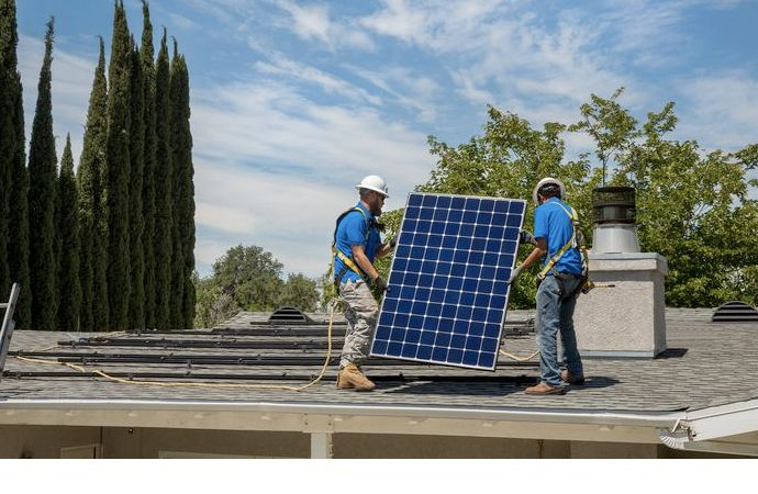 solar installers carrying a solar panel