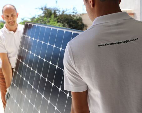 Installers carrying solar panel